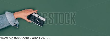 Banner With Female Hand Holding Old Retro Photo Camera On Green Background With Copy Space For Text.
