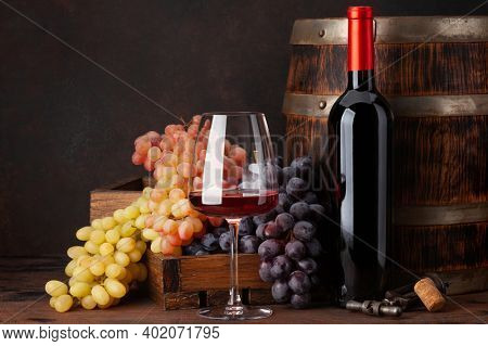 Wine bottle, grapes, glass of red wine and old wooden barrel. With copy space