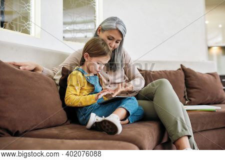 Asian Grandma Sitting Beside Little Granddaughter With Digital Tablet On Sofa At Home. Generation An