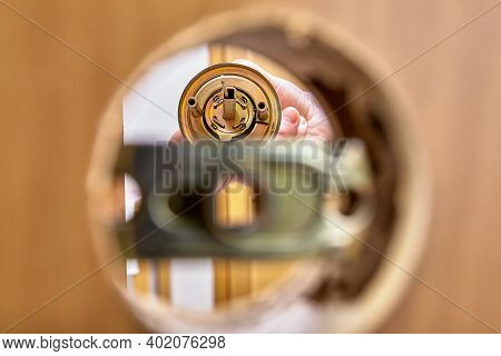 View Of Doorknob Rose With Spindle Through Mounting Hole In Door And Latch Assembly.