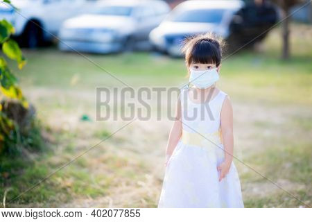 Girl In A White Dress Stands In A Parking Lot In A Rural Area. Children Wear A Surgical Face Mask To