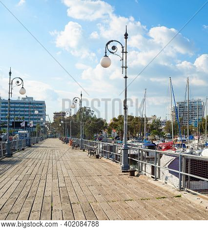 Wooden Pier Of Marina With Moored Yachts And Motorboats, Hotels And Apartments Buildings In Bright E