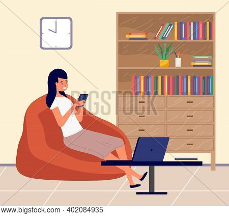 Young Girl Looking At Mobile Phone And Checking Social Networks Sitting In Cozy Armchair In Livingro