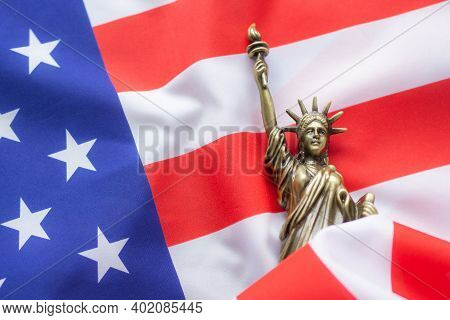 A Replica Of The Statue Of Liberty Placed On The Usa Flag. There Is Lighting On The Side Of The Stat