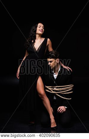 Full Length Of Cheerful Woman In Dress Standing With Tied Submissive Man In Suit On Black