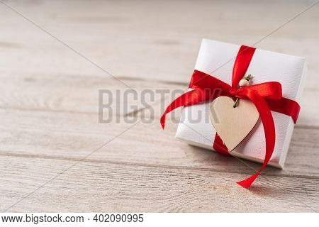 Gift Or Present Box With Red Bow And Heart On Wooden Background. Pastel Colors, Copy Space For Text