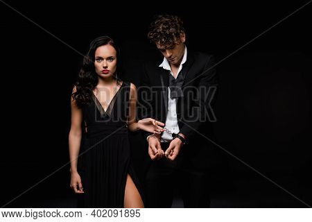 Sexy Woman In Dress Holding Handcuffs On Submissive Man Isolated On Black
