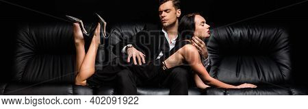 Man In Suit Seducing Sexy Woman Lying On Sofa Isolated On Black, Banner