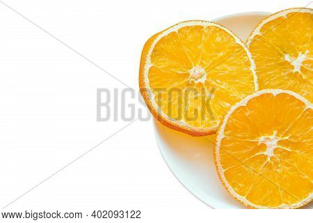 Plate With Three Slices Of Dried Orange Isolated On A White Background With Place For Text. Copy Spa