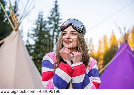 Portrait Of Pretty Caucasian Young Woman Near The Indian Tipi Or Wigwam In Ski Outfit And Winter Spo