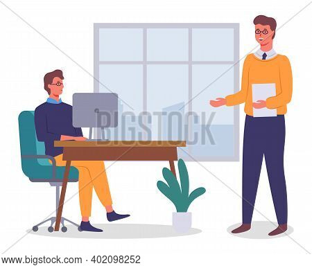 Office Workers. Colleagues Communicating. Executive Guy Talking With Man Sitting At Table Using Comp