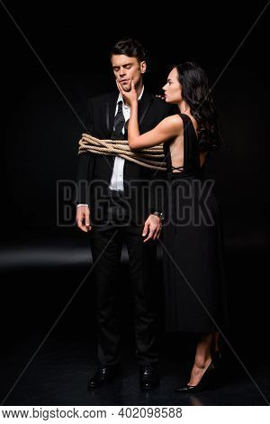 Dominant Woman In Dress Touching Face Of Tied Submissive Man In Suit On Black