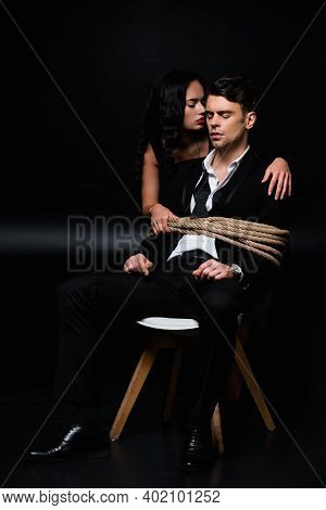 Brunette Woman In Dress Near Tied Submissive Man Sitting On Chair On Black