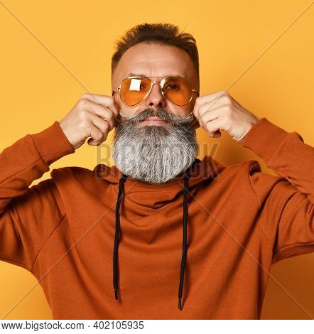 Brutal Bearded Hipster Man In Casual Sportswear, Trendy Sunglasses Twirling Mustache And Looking At