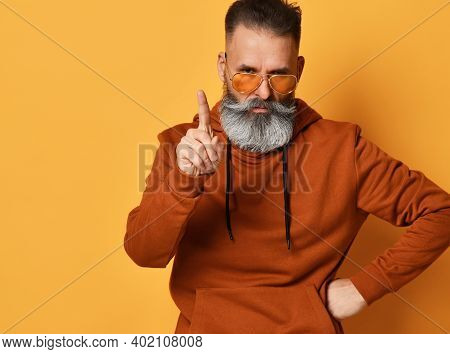 Frowning Menacing Brutal Grey-haired Bearded Man In Sportswear And Trendy Sunglasses Rejecting Offer