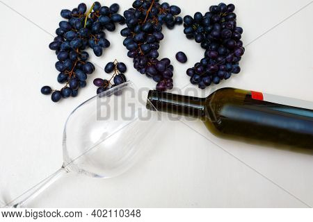 Bunches Of Grapes With A Bottle Of Wine And A Glass On A White Background. Harvesting Grapes And Pre