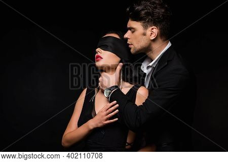 Man In Suit Choking Blindfolded Woman In Dress Isolated On Black