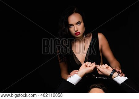 Sexy Woman In Dress Near Submissive Handcuffed Man Isolated On Black