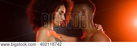 Side View Of Shirtless African American Man Seducing Curly Woman On Black, Banner