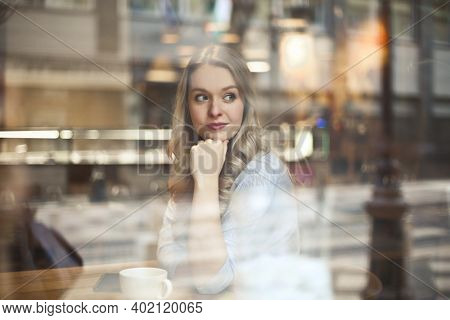 portrait of beautiful woman through a glass of a cafè
