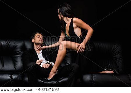 Sexy Woman In High Heel Shoes Touching Submissive Man In Handcuffs Isolated On Black