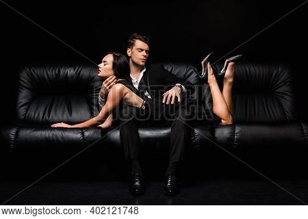 Man In Formal Wear Seducing Sexy Woman Lying On Sofa Isolated On Black