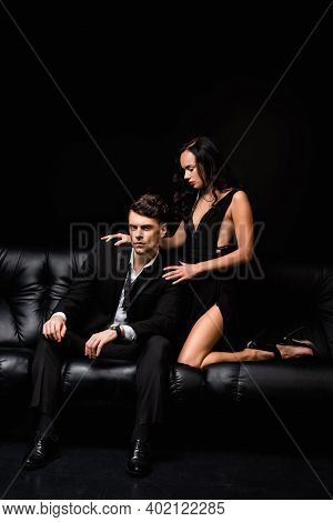 Brunette Woman In Dress Seducing Man In Suit Sitting On Sofa On Black
