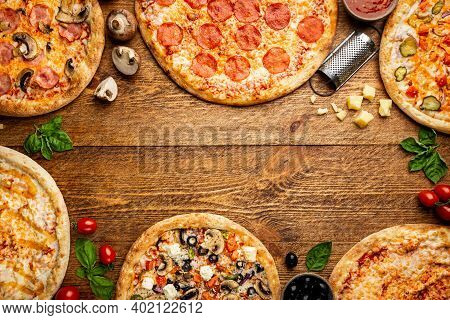 Flat-lay Of Different Types Of Pizza And Red Wine Over Rustic Wooden Table, Top View. Fast Food Lunc