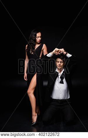 Full Length Of Sexy Woman In Dress Looking At Submissive And Handcuffed Man Standing On Knees On Bla