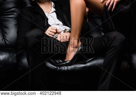 Cropped View Of Sexy Woman In High Heel Shoe On Sofa With Submissive Man In Handcuffs