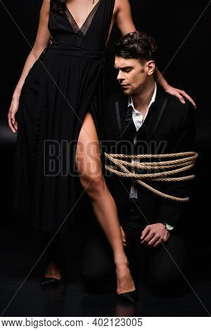 Dominant Woman In Dress Standing Near Tied Submissive Man In Suit On Black
