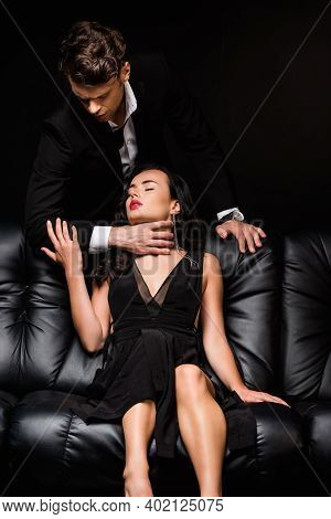 Dominant Man In Formal Wear Choking Sexy Woman Isolated On Black