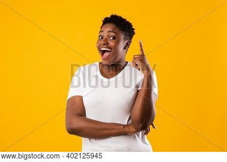 Cheerful Overweight Black Woman Pointing Finger Up Having Great Idea Posing Smiling To Camera Standi