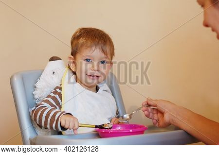 Little Boy Sitting At A Chair For Feeding And Smiles. He Holds A Spoon In His Hand And Tries Himself