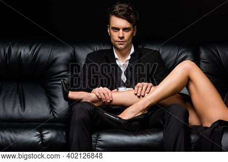 Legs Of Seductive Woman In High Heels Lying On Man In Suit Isolated On Black