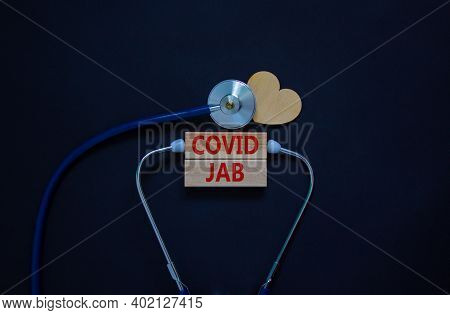 Covid Jab Symbol. Wooden Blocks With Words 'covid Jab' And Stethoscope On Black Background. Wooden H