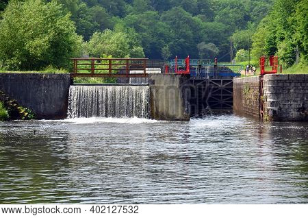 Weir with lock and lock gate in the picturesque river Yonne in Burgundy, France. The Yonne is particularly popular with pleasure craft.