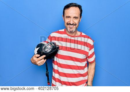 Middle age handsome motorcyclist man holding moto helmet over isolated blue background looking positive and happy standing and smiling with a confident smile showing teeth