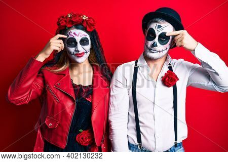 Couple wearing day of the dead costume over red pointing unhappy to pimple on forehead, ugly infection of blackhead. acne and skin problem