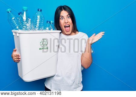 Young beautiful woman recycling plastic bottles on wastebasket to care environment celebrating achievement with happy smile and winner expression with raised hand