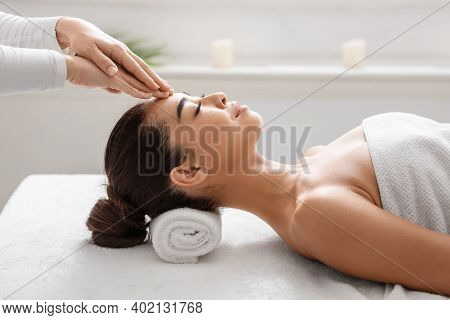 Spa Treatment. Calm Asian Woman Enjoying Relaxing Acupressure Head Massage By Professional Therapist