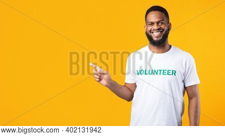 Black Male Volunteer Pointing Finger Aside Smiling To Camera Standing Over Yellow Studio Background.