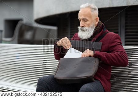 Aged Grey-haired Man In Suit Sitting On Bench, Getting Gadget Laptop Or Digital Tablet Out Of Leathe