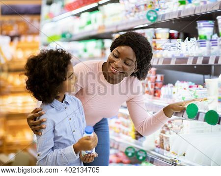 Young Black Mother With Her Daughter Shopping For Dairy Products At Supermarket. Cute Girl With Her