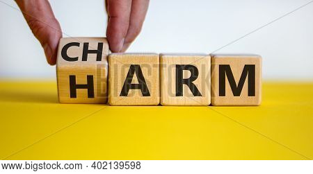 From Harm To Charm. Male Hand Turns The Cube And Changes Word 'harm' To 'charm'. Beautiful Yellow Ta