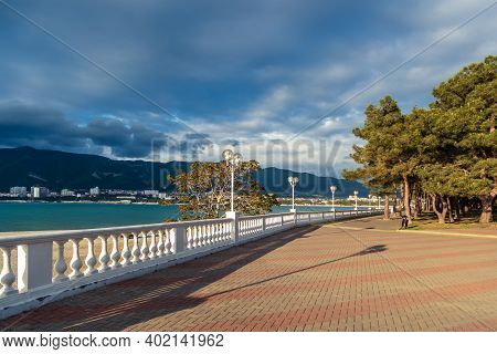 A White Balustrade Casts Beautiful Shadows At Sunset On The Embankment. Mountains And Sea In The Bac