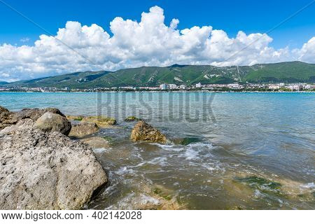 Stones On The Shore Of Gelendzhik Bay. Clear Sunny Day. Mountains And White Curly Clouds In The Back