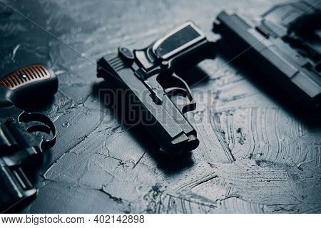 Group Of Pistols On Black Concrete Table. Vintage Revolver With A Drum. 9mm Handgun. Several Types O