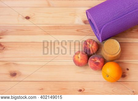 Yoga Mat, Fresh Fruits And Homemade Healthy Fruits Smoothie Made Of Oranges, Peaches And Bananas On