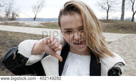 European Woman Shows Disapproval Sign, Gives Thumb Down Gesture, Dislikes Something, Has Disgusting